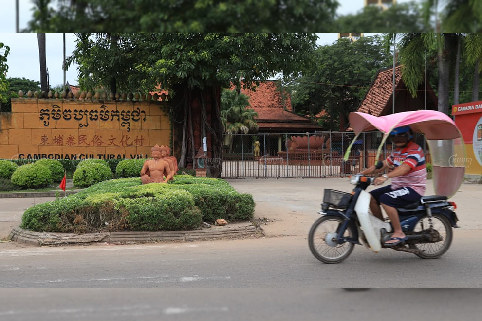 A motorist rides past the closed gates of the Cambodian Cultural Village in Siem Reap on November 11. Panha Chhorpoan