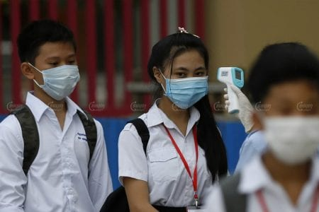 A student from Bak Touk high school in Phnom Penh has her temperature checked before entering the classroom in September. Panha Chhorpoan