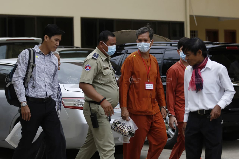 Former RFA journalists Yeang Sothearin, left, and Uon Chhin, right, and RT fixer Rath Rott Mony, center, leave the Supreme Court in Phnom Penh after a hearing on July 1. Panha Chhorpoan