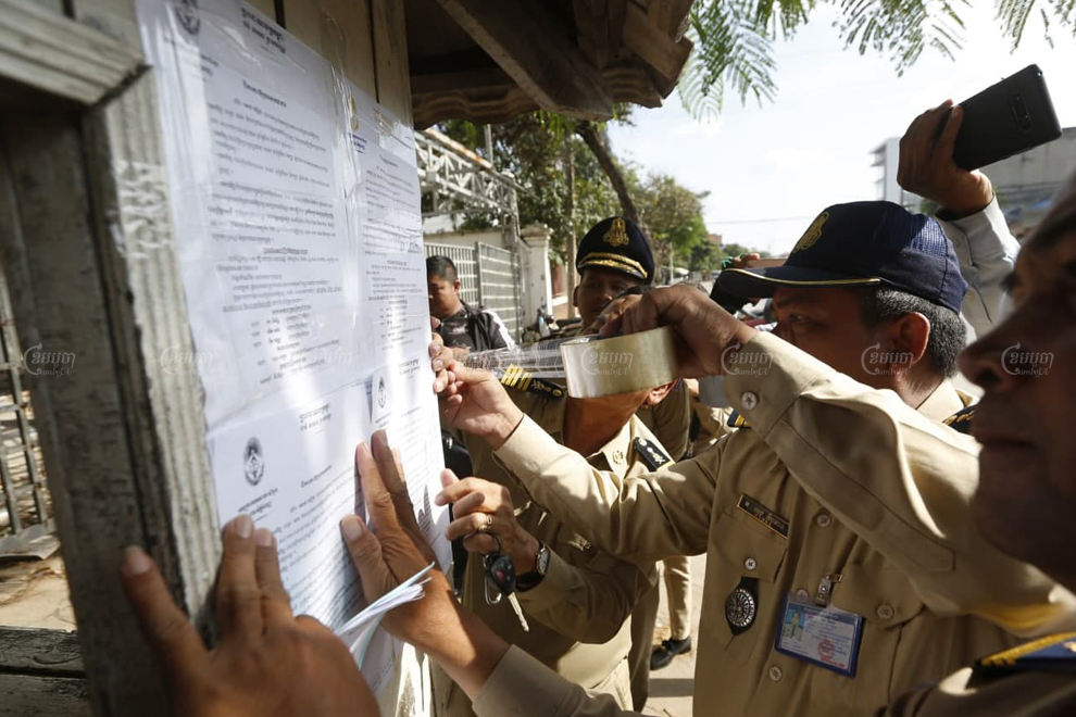 Phnom Penh police officials plaster court summons for former CNRP members at the party headquarters earlier this month for hearings that will be conducted on November 26. Panha Chhorpoan