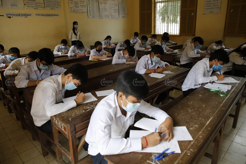 Students take the Grade 9 national examination at Sisowath high school on Monday, as a new COVID-19 cluster resulted in the Education Ministry cancelling the rest of the school year. Panha Chhorpoan
