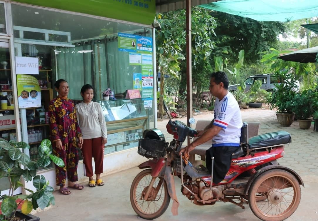 People affected by severe flooding in September and October receive humanitarian aid from two non-governmental groups at a cash transfer service in Siem Reap province. DCA