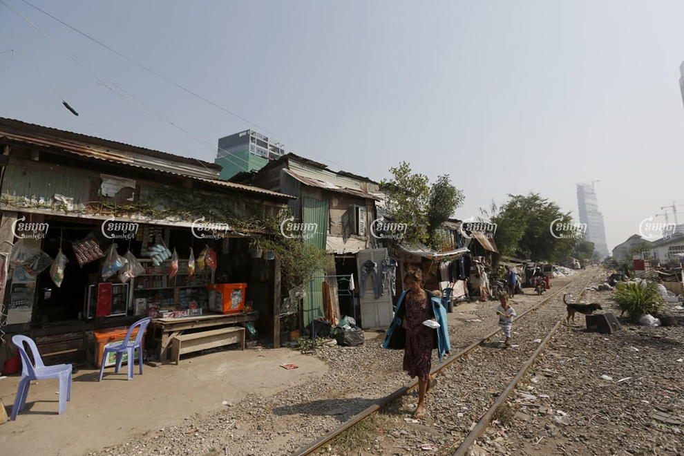 A resident and her child kid walk along the railway line in Toul Kork district on January 15. Panha Chhorpoan