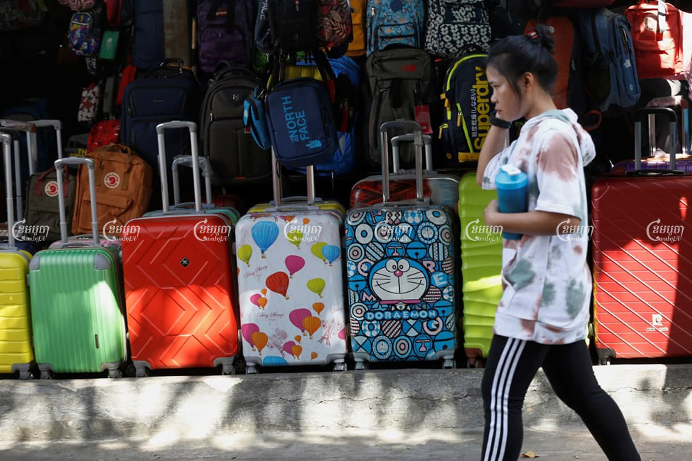 A woman walk pass suitcase shop in Phnom Penh on January 9, 2021. Travel goods exports will be tariffed till the U.S reauthorizes the GSP program. Panha Chhorpoan