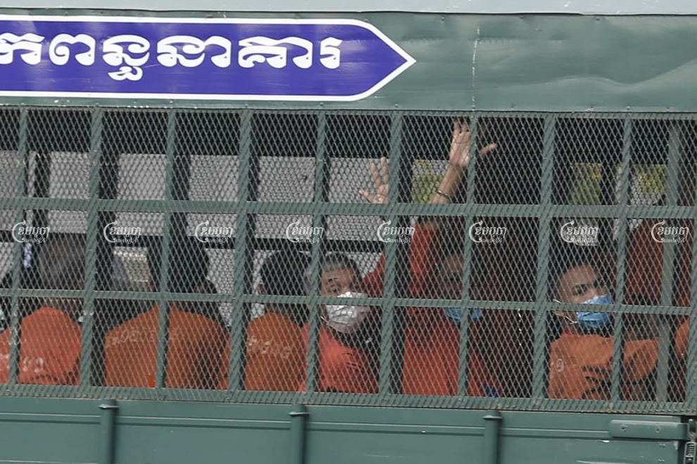 Former CNRP official Sok Chantha waves to photographers as he arrives at the Phnom Penh Municipal Court in a prison truck on Friday. Panha Chhorpoan