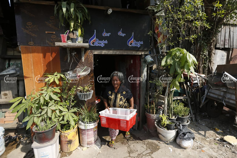 Iev Mach walks out of her home, which is set to be demolished to make way for a new road, in Toul Kok district on January 15. Panha Chhorpoan