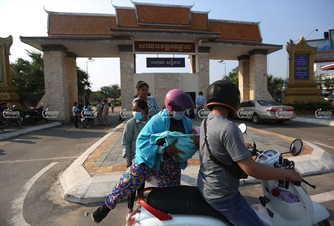 A garment worker carries her son to ride a motorcycle after receiving compensation at the Kandal Provincial Hall on Friday. CamboJA/ Pring Samrang