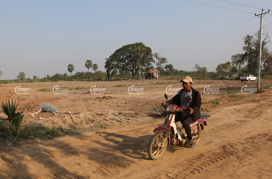 A villager rides past the disputed land in Kandal province's Ksach Kandal district on February 16. CamboJA/Pring Samrang