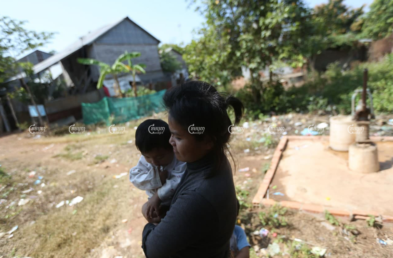 Chey Sopheak, a former resident of Borei Keila, carries her child near her Sras Por village home in February 2021. Her hair is short because she sold it to pay for medical treatment. CamboJA/ Pring Samrang