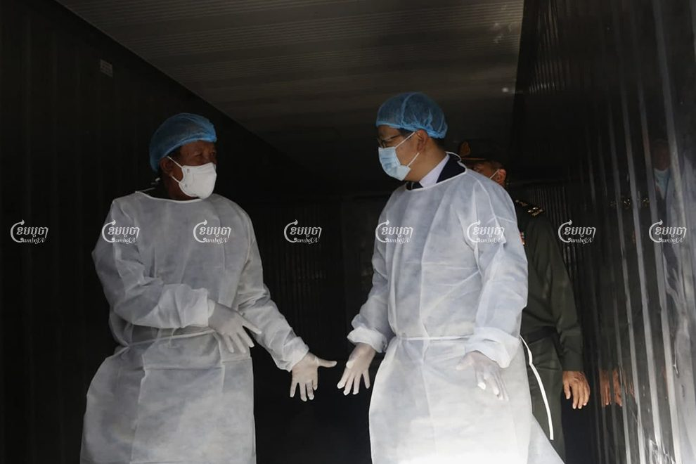 Defense Minster Tea Banh and Chinese Ambassador Wang Wentian are dressed in PPE during a visit to Preah Ket Melea Hospital in Phnom Penh on Wednesday. Panha Chhorpoan