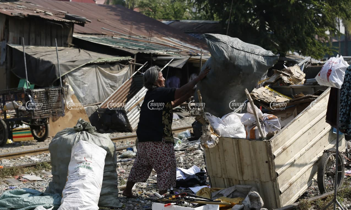Iev Mach empties recyclables into a cart near her home in Toul Kok district, where her community is facing eviction to make way for a new road and drainage system, on January 15. Panha Chhorpoan