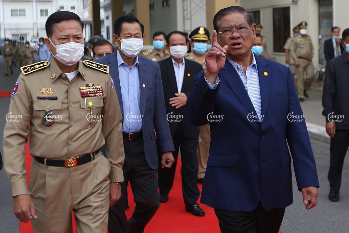 Interior Minister Sar Kheng speaks with National Police Commissioner Neth Savoeun at a ceremony to hand over vehicles to provincial police commissariats, at the Interior Ministry on Tuesday. CamboJA/Pring Samrang