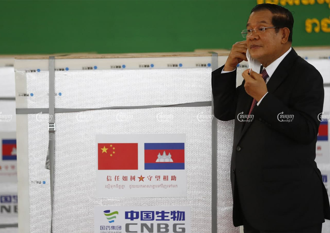 Prime Minister Hun Sen stands in front of a shipment of vaccines at a ceremony to mark their arrival from China at the Phnom Penh International Airport last week. CamboJA/Pring Samrang