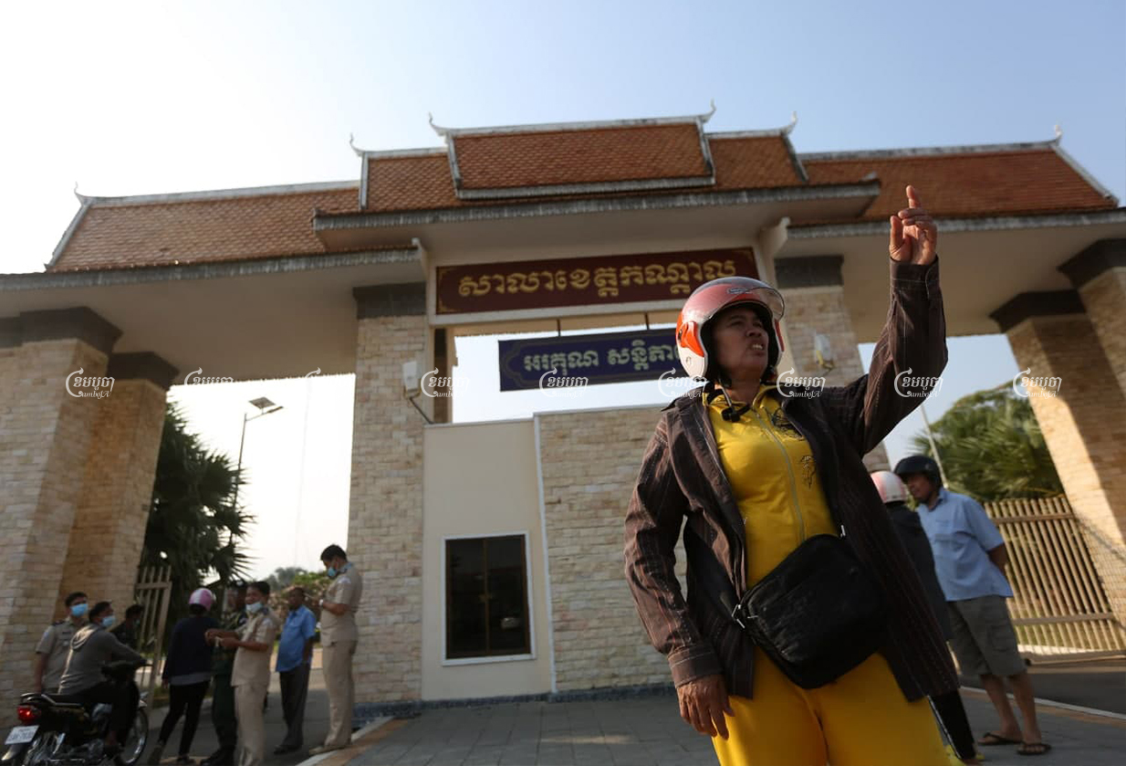 Sao Na stands in front of the Kandal Provincial Hall on Friday before receiving compensation along with 1,000 others in a long-running dispute with her former employer. CamboJA/Pring Samrang