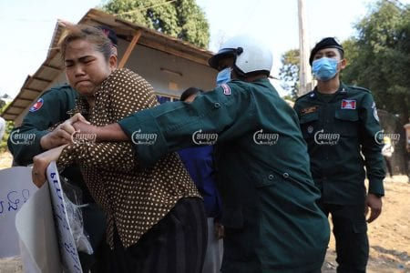 Siem Reap police manhandle a villager on Saturday protesting the demolition of her house in the province's Siem Reap city. Panha Chhorpoan