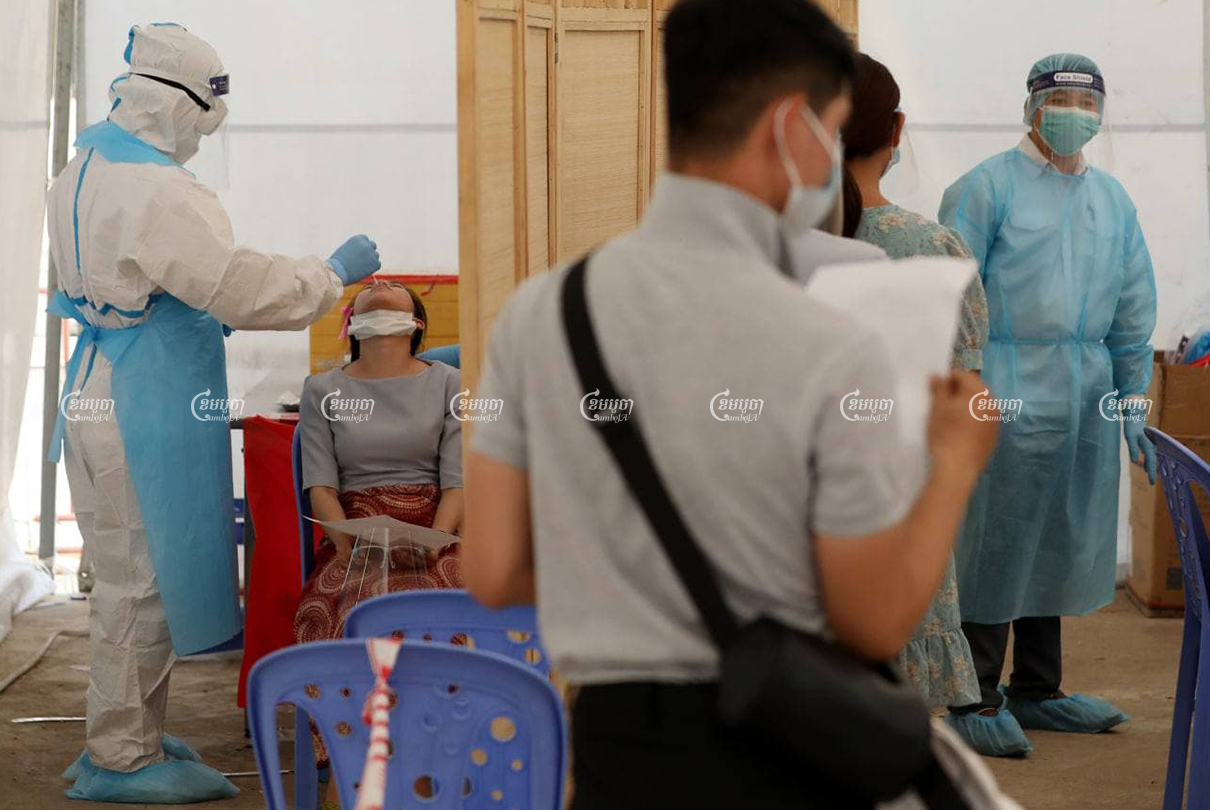 A healthcare worker collects a sample from a woman for a COVID-19 test on Tuesday at Phnom Penh's Chak Angre Health Center. CamboJA/ Pring Samrang