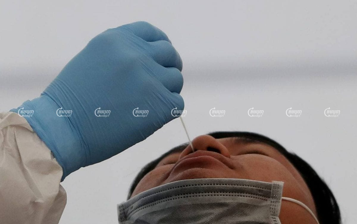 A healthcare worker swabs a man's nasal cavity for a COVID-19 test on Tuesday at Phnom Penh's Chak Angre Health Center. CamboJA/ Pring Samrang