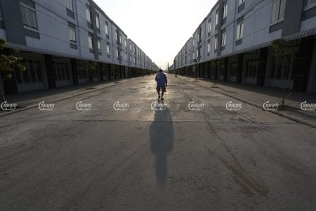 A man walks past houses in a Phnom Penh borey on March 23. CamboJA/Panha Chhorpoan