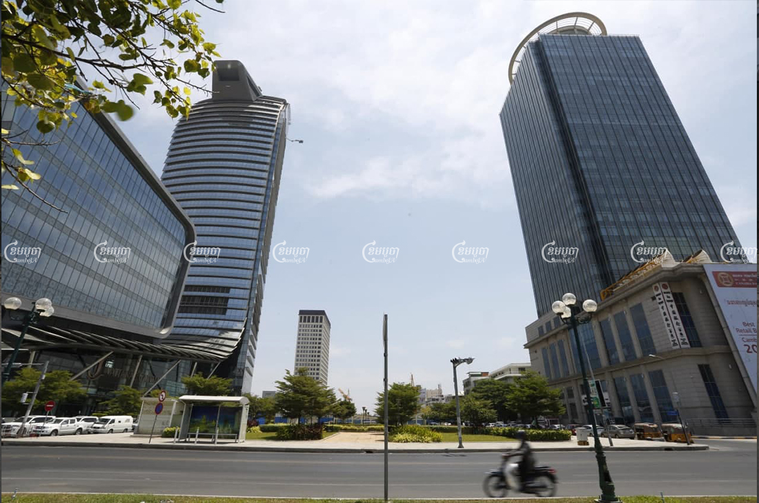A motorist rides past the Canadia Bank and Vattanac Bank head offices in Phnom Penh on March 24. CamboJA/Panha Chhorpoan