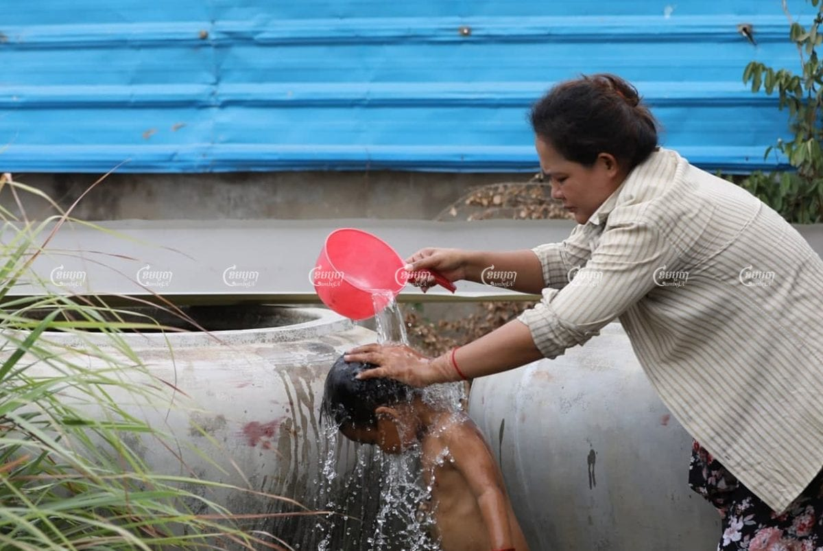 A woman showers a child in water purchased from a private company in outer Phnom Penh, March 21. CamboJA/Pring Samrang