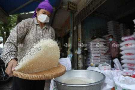 A woman sifts through rice at a store in Phnom Penh on March 25.CamboJA/Pring Samrang
