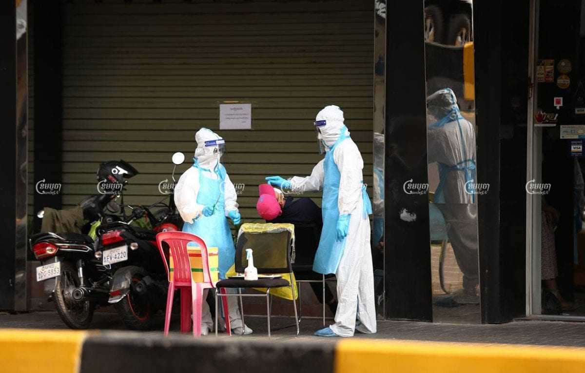Health workers conduct a COVID-19 test on Monday outside a clothing shop in Phnom Penh. Panha Chhorpoan