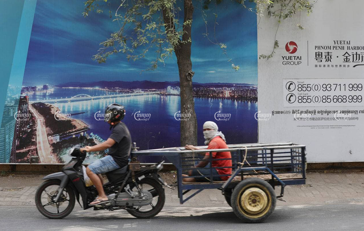 Motorists pass by an advertisement for the Yuetai Group's City Gate development, in Phnom Penh, on February 24. CamboJA/Pring Samrang