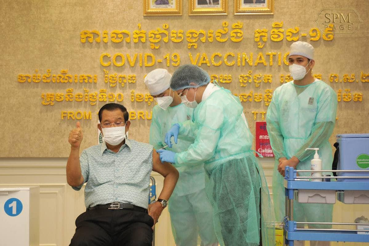 Prime Minister Hun Sen gives a thumbs up to reporters as he gets his first dose of the AstraZeneca vaccine on Thursday at Phnom Penh's Calmette Hospital. Hun Sen's Facebook