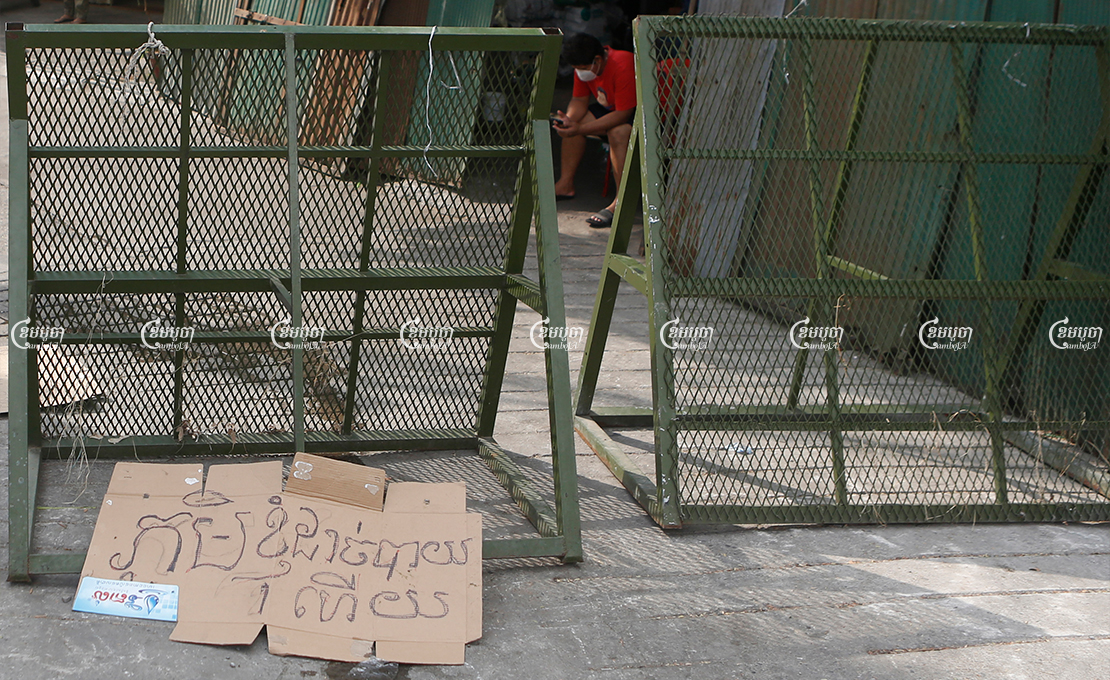 "A banner left by a protester reading ""My village runs out of food"" is seen near barriers at a red zone in Phnom Penh, April 30, 2021. CamboJA/ Panha Chhorpoan"
