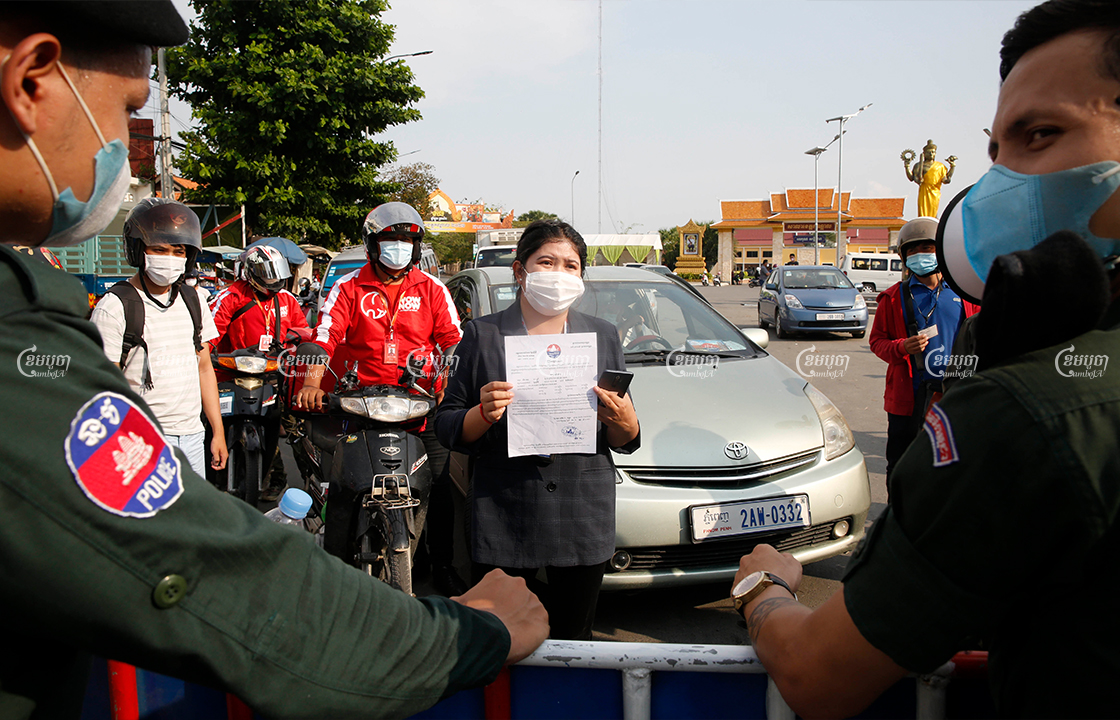 A female journalist displays a travel permission letter to police at the Phnom Penh-Kandal Police barricade of the first day of lockdown, April 15, 2021. CamboJA/ Panha Chhorpoan