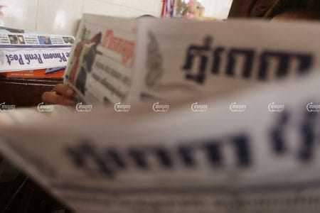 A woman reads the print edition of the Phnom Penh Post newspaper, which stopped the presses during Phnom Penh lockdown, April 20, 2021. CamboJA/ Pring Samrang