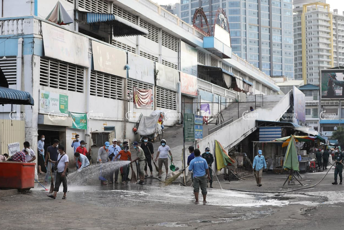 Authorities and security guards clean at O'Russei Market, which was closed Sunday after vendors and security guards tested positive for COVID-19, in Phnom Penh, April 4, 2021. CamboJA/ Pring Samrang