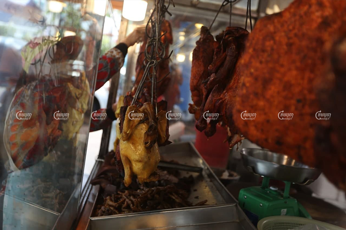 Before the start of the night's curfew, a vendor prepared roast duck, chicken and pork for sale at a street stall in Phnom Penh, April 2, 2021. CamboJA/ Pring Samrang