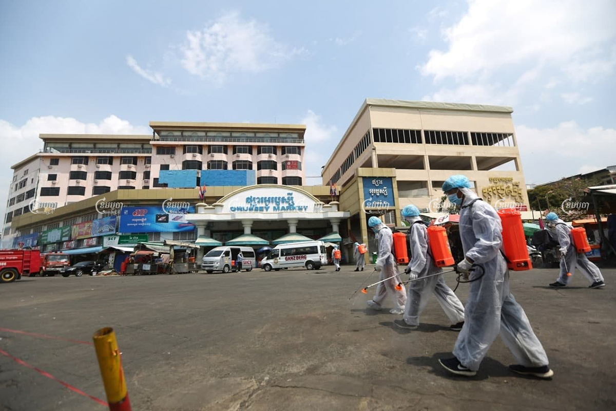 Healthcare workers disinfect the roads in front of O'Russei market, which was closed after vendors and security guards tested positive for COVID-19, in Phnom Penh, April 5, 2021. CamboJA/ Pring Samrang