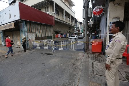 Residents walk past a barrier placed in front of a Phnom Penh road, April 19, 2021. CamboJA/ Pring Samrang