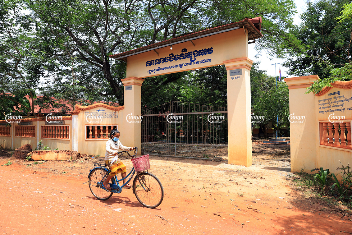 A girl rides a bicycle past a primary school in Siem Reap province's Puok district, May 7, 2021. CamboJA/ Panha Chhorpoan