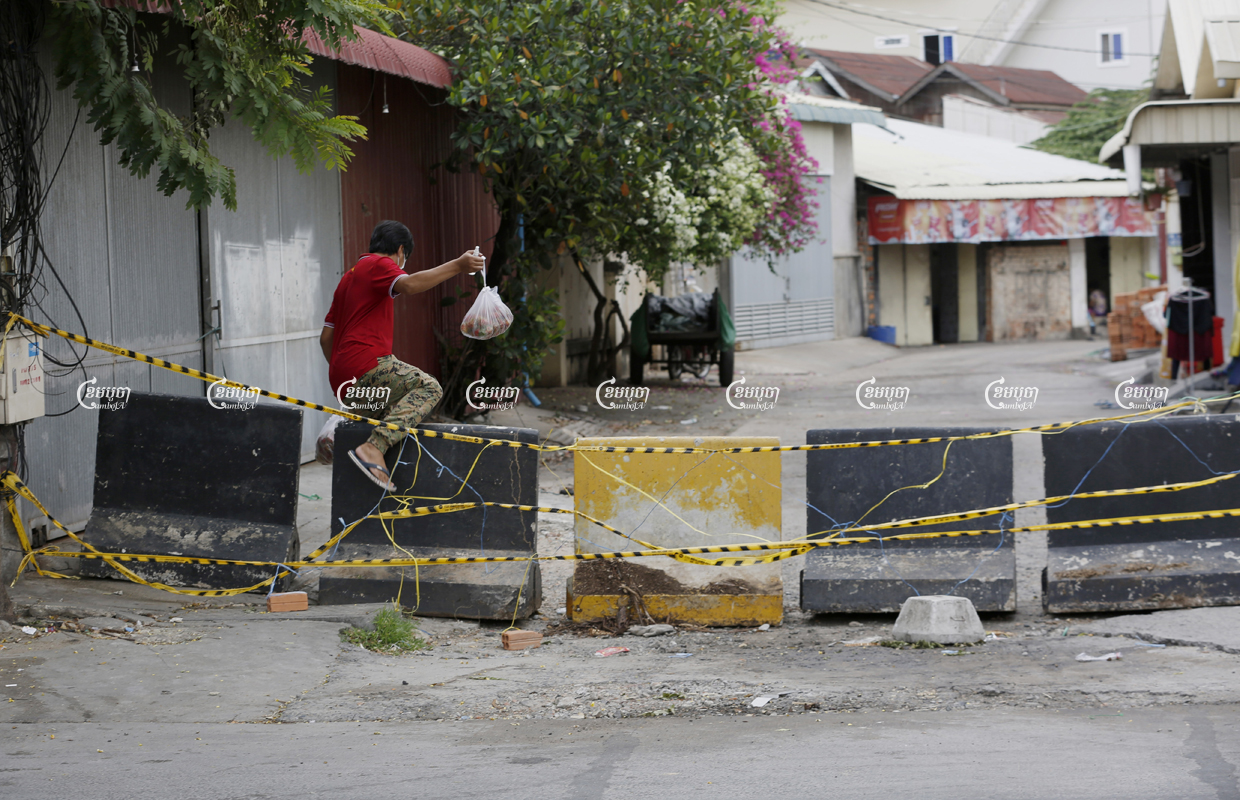 A man crosses a barricade blocking a Phnom Penh red zone, April 30, 2021. CamboJA/ Panha Chhorpoan