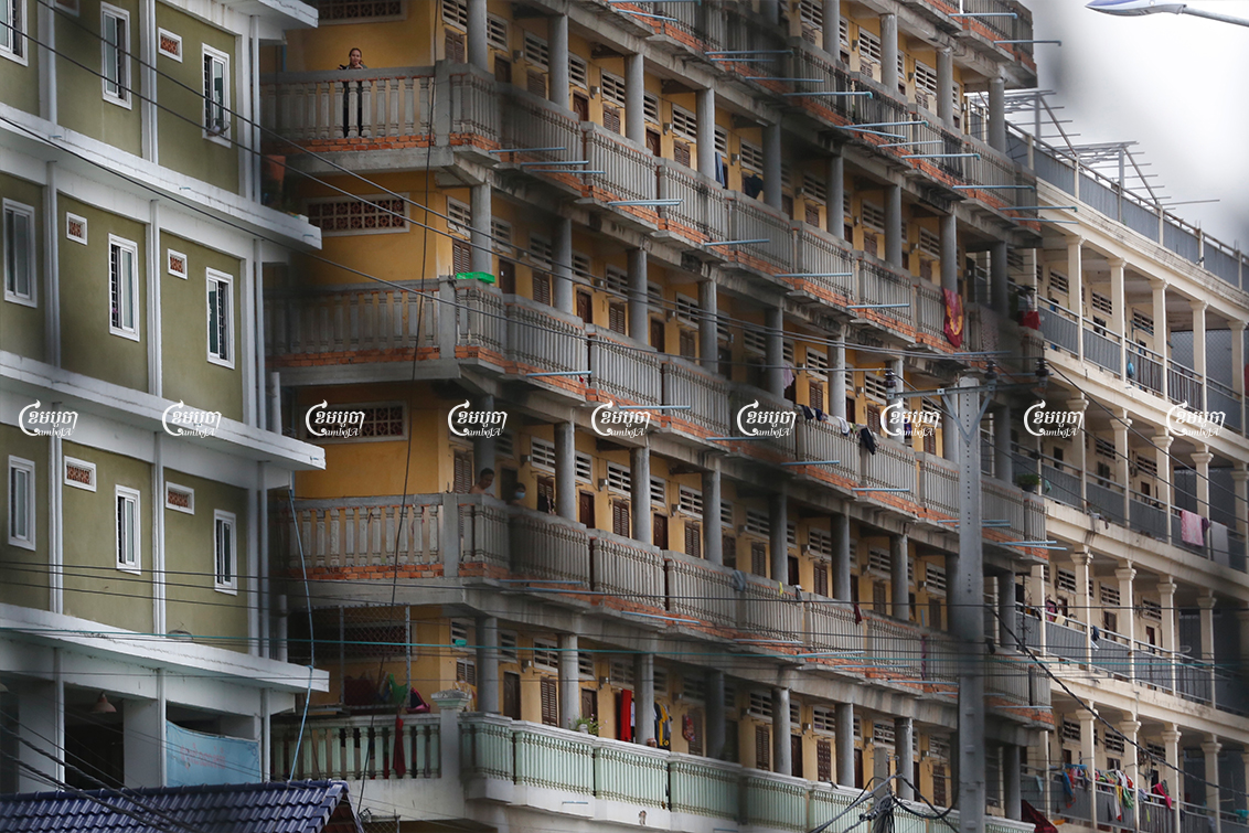 After a small Monday morning protest in their neighborhood demanding rent exemptions, suspended garment workers stand on the balconies of their rental apartments within a red zone at the Stung Meanchey III commune in Phnom Penh, May 10, 2021. CamboJA/ Panha Chhorpoan