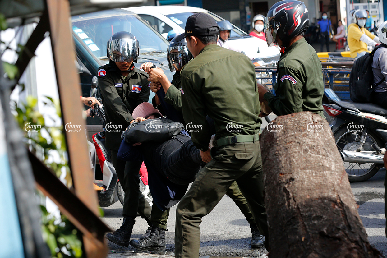 District security guards carry a protester away from a demonstration marking the Paris Peace Agreements Day outside the Chinese Embassy in Phnom Penh on October 23. CamboJA/ Panha Chhorpoan