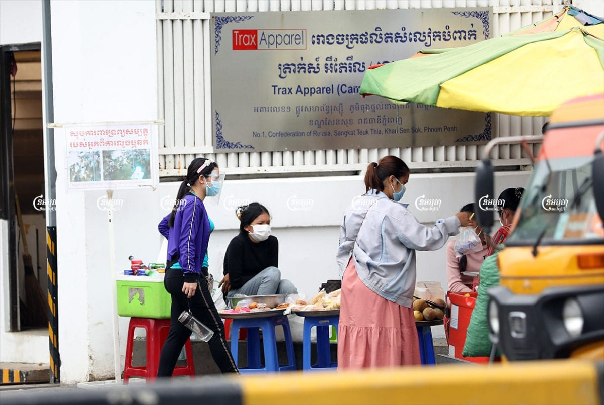 Garment workers at their lunch break outside a factory where workers recently tested positive for COVID-19, in Phnom Penh, May 24, 2021. CamboJA/ Pring Samrang