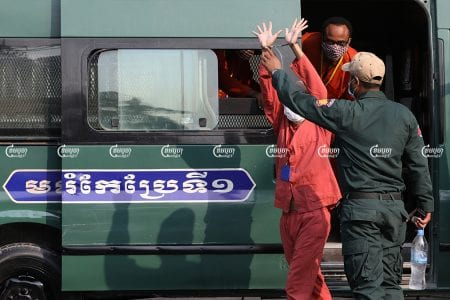 Inmates leave a crowded prison van on their way to a hearing at Phnom Penh Municipal Court, March 31, 2021. CamboJA/ Pring Samrang