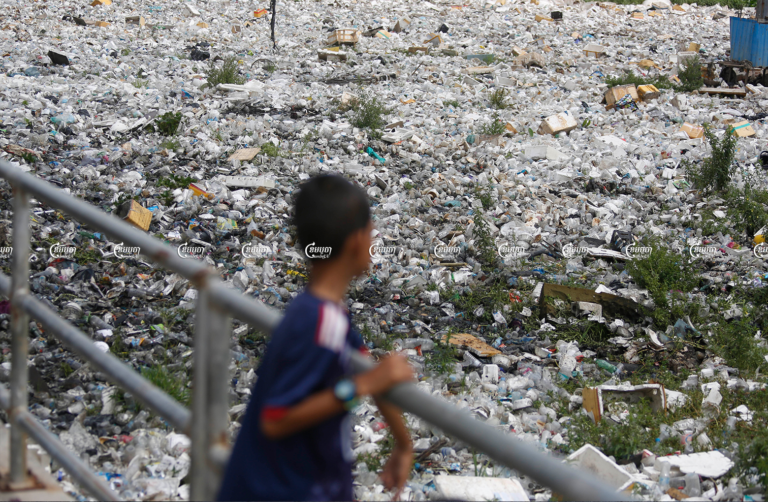 A boy looks at the garbage filling Boeung Tompun lake, a wetland that has been taken over by a massive development, Picture taken on June 28, 2018. CamboJA/ Pring Samrang
