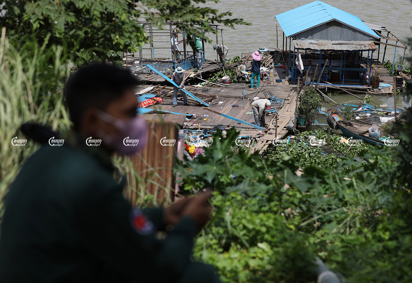 A police officer monitors ethnic Vietnamese people while they move their floating house in Chroy Changvar district, June 14, 2021. CamboJA/ Pring Samrang