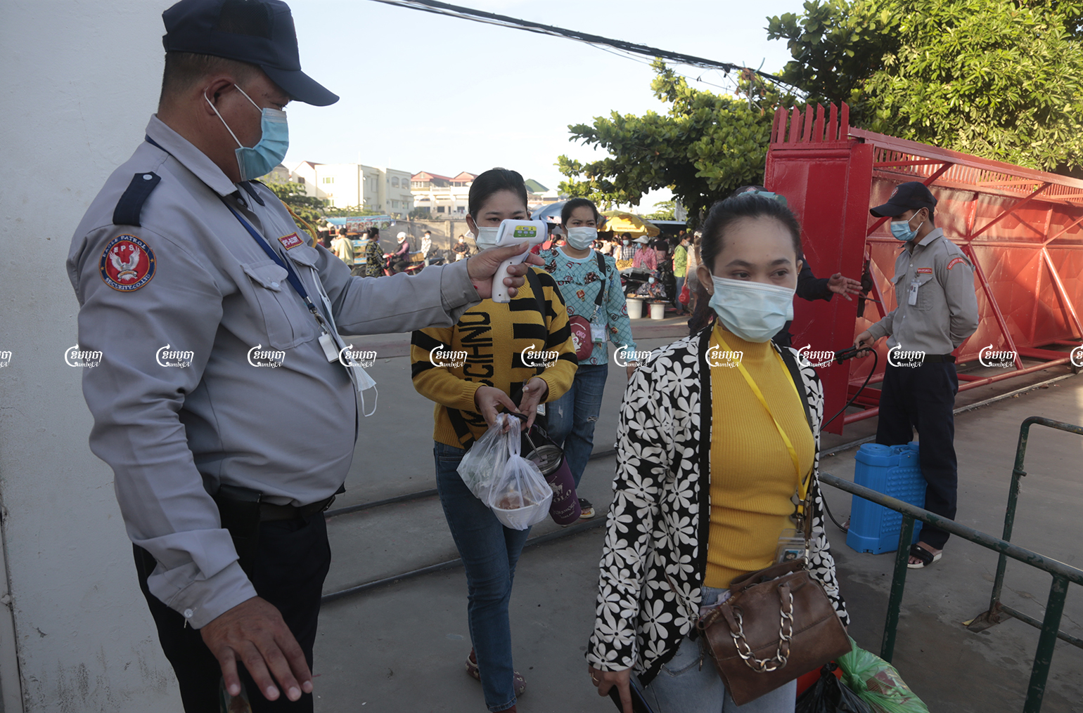 Garment workers get their temperature checked as they arrive at their factory in Phnom Penh, June 14, 2021. CamboJA/ Panha Chhorpoan