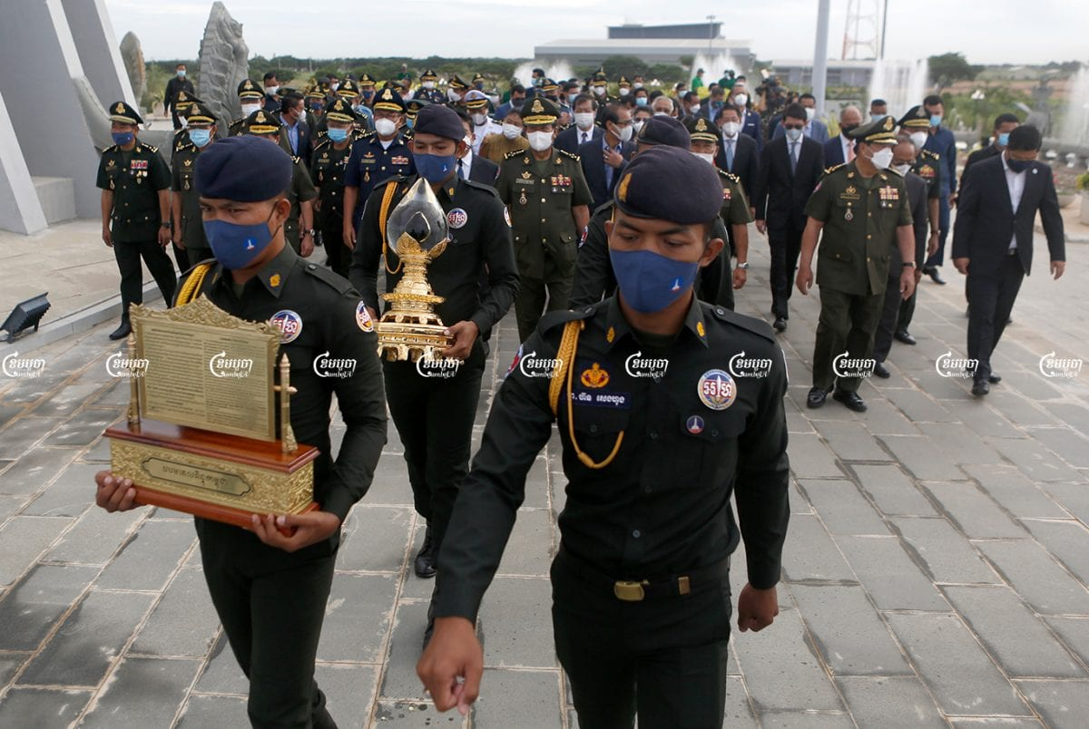 Soldiers carry Cambodia's first drop of crude oil during a ceremony at Phnom Penh's Win Win Monument, June 9, 2021. CamboJA/ Panha Chhorpoan