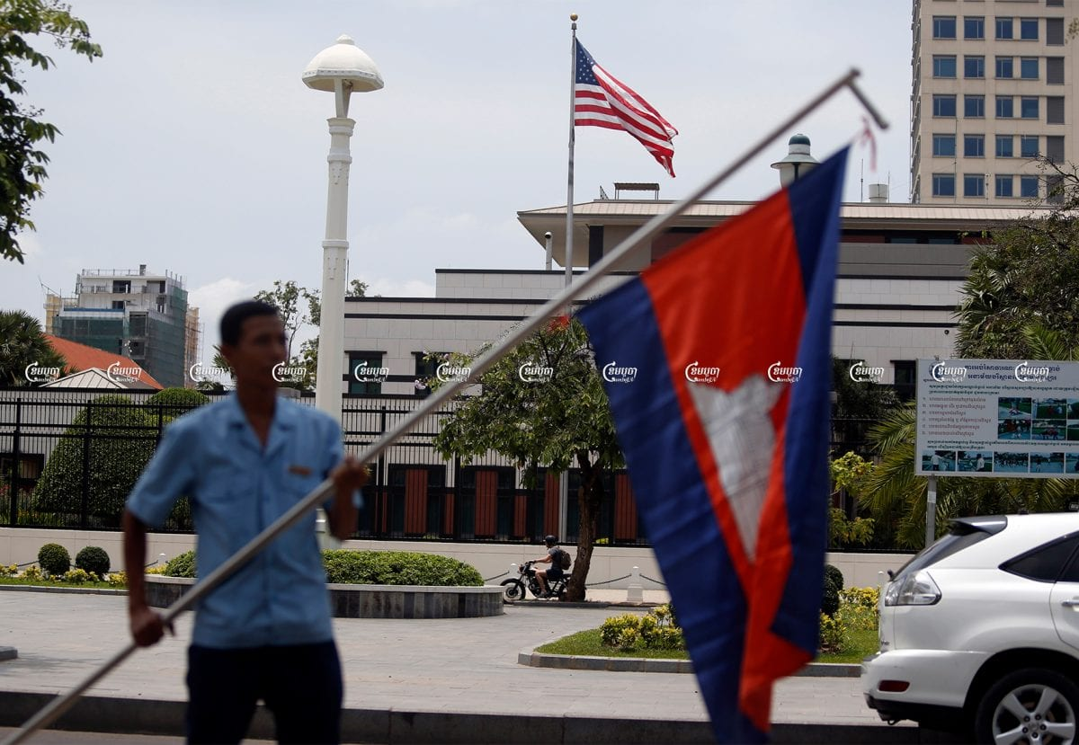 A man holds a Cambodian flag in front of the U.S. Embassy in Phnom Penh, Picture taken on April 13, 2018. CamboJA/ Pring Samrang
