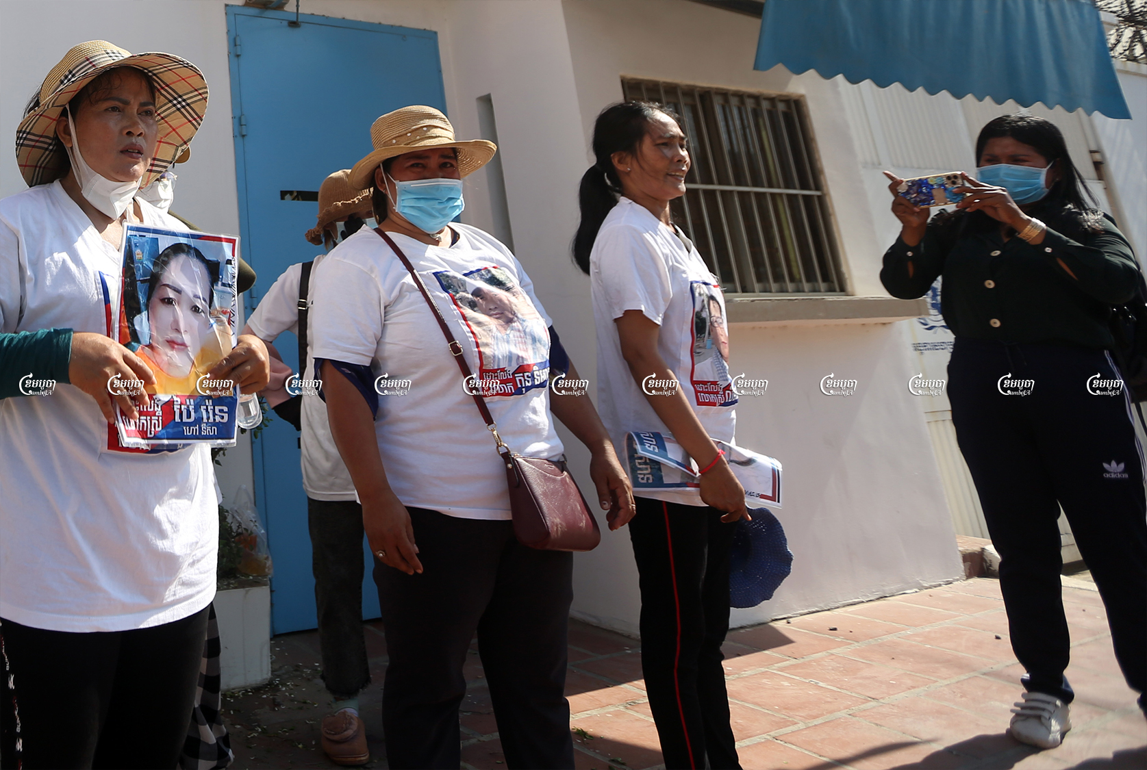 A woman broadcasts a Facebook live video of a protest outside the UN office in Cambodia carried out by family members of former opposition activists. Picture taken on June 4, 2021. CamboJA/ Pring Samrang