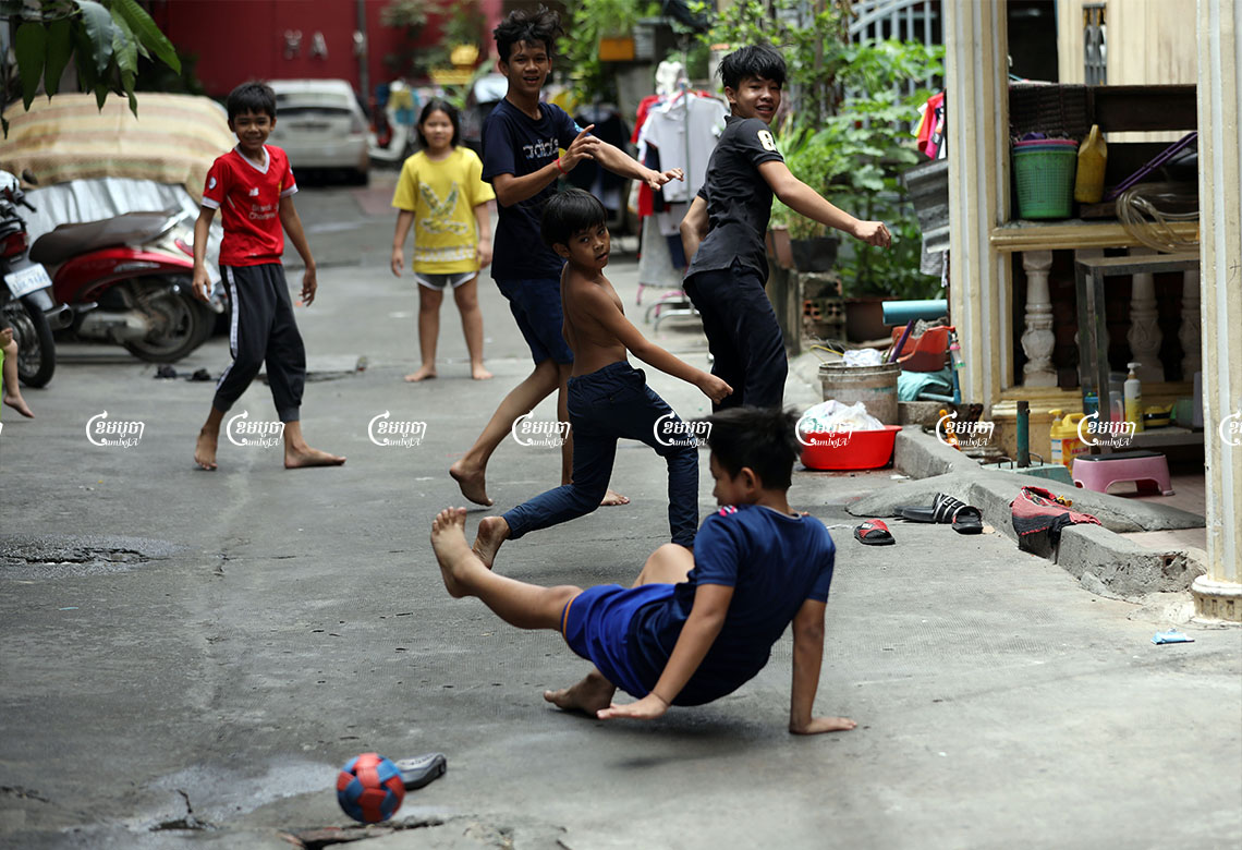 Children play football at a village in Phnom Penh. Cambodia's PM Hun Sen says the country wants to begin offering COVID-19 vaccinations to children, July 16, 2021. CamboJA/ Pring Samrang