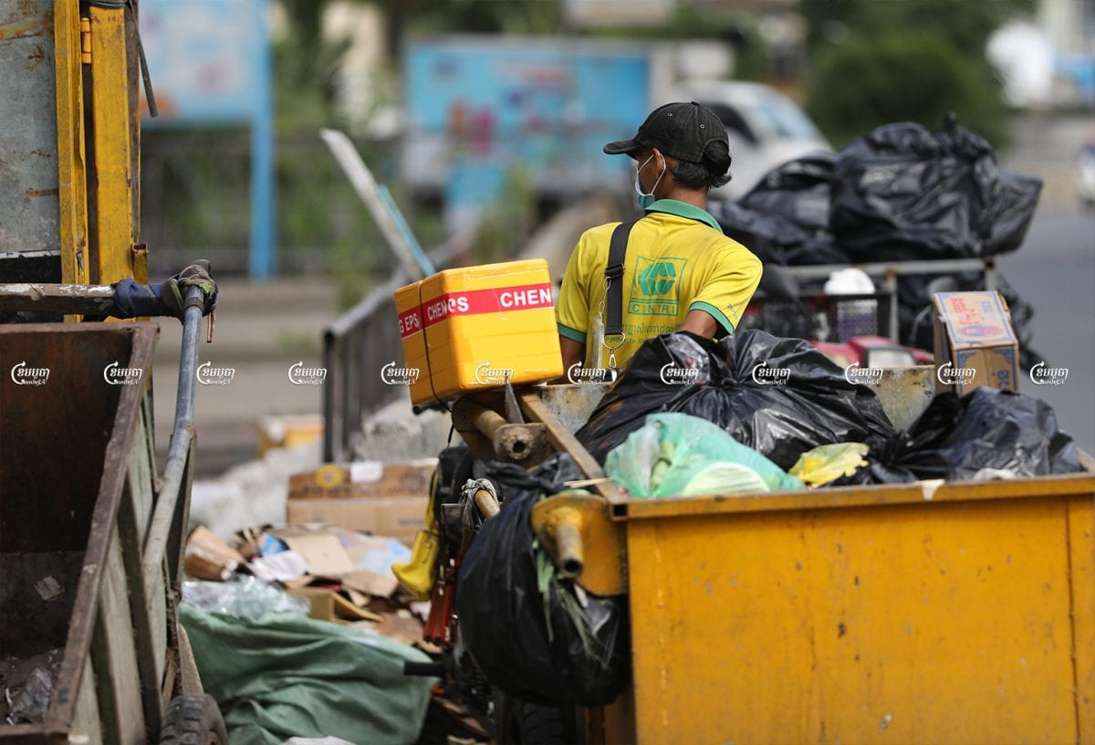Cintri workers collect garbage along a street in the Chamkar Mon district of Phnom Penh, July 8, 2021. CamboJA/ Pring Samrang