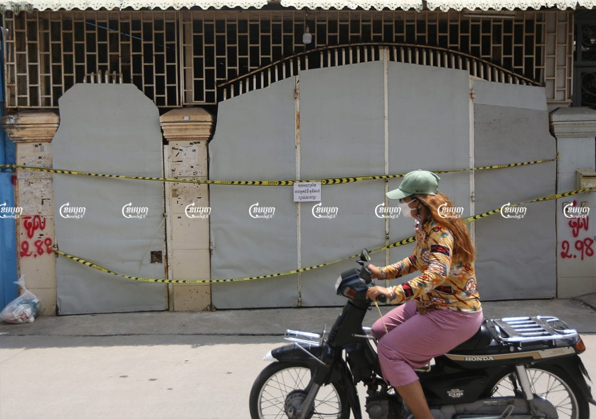 Motorists drive past a house where people are undergoing home treatment for Covid-19 in Phnom Penh, July 12, 2021. CamboJA/ Pring Samrang